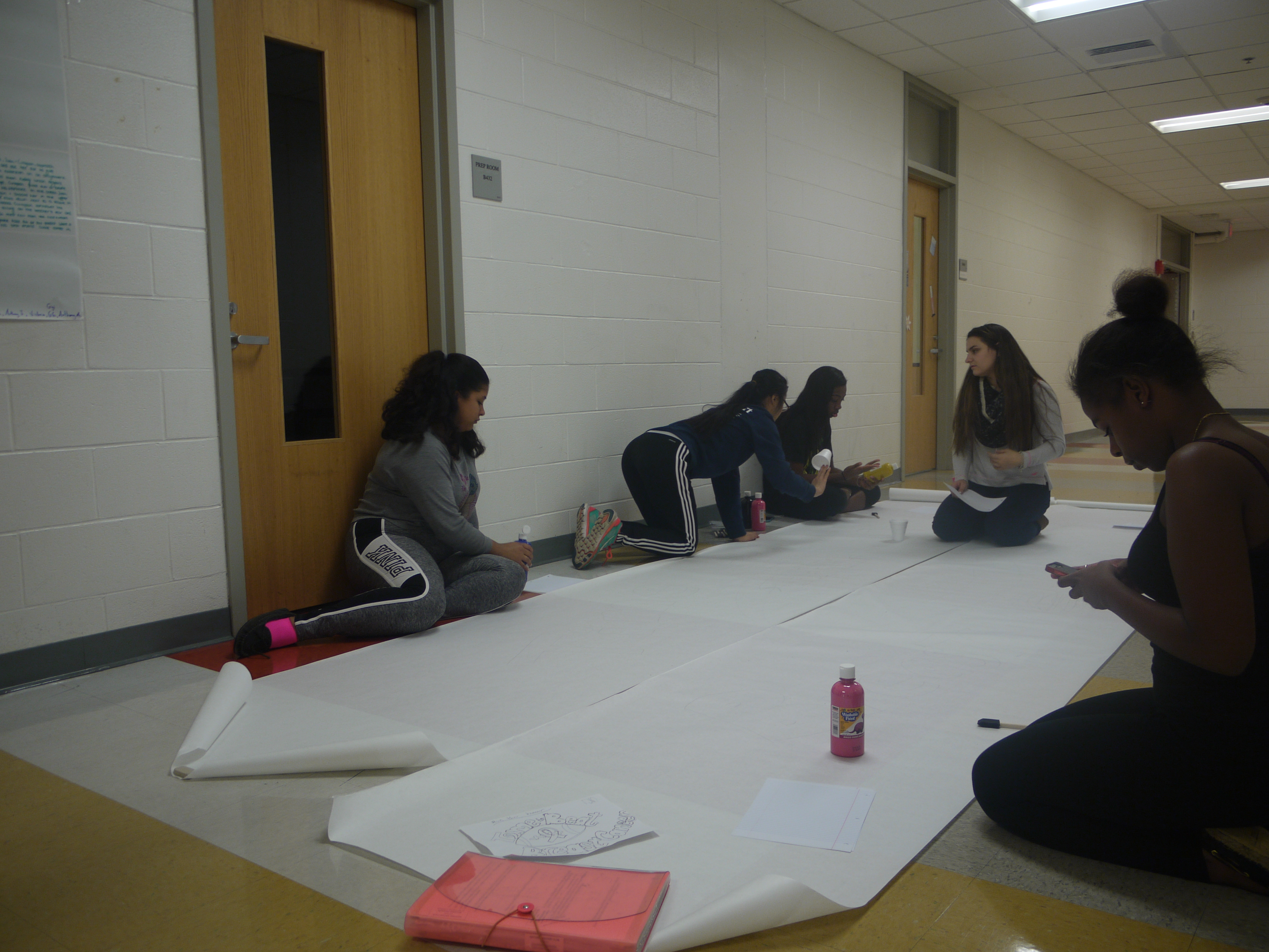 Malden Against Cancer members making the banner for the pink-out football game. Photo taken by Josandy Jeune.